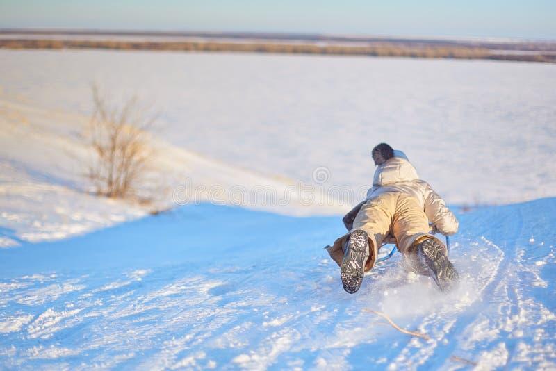 乘坐雪撬的快乐的女孩下坡在一个白色晴朗的冬天山风景的一串积雪的爬犁足迹 免版税库存图片