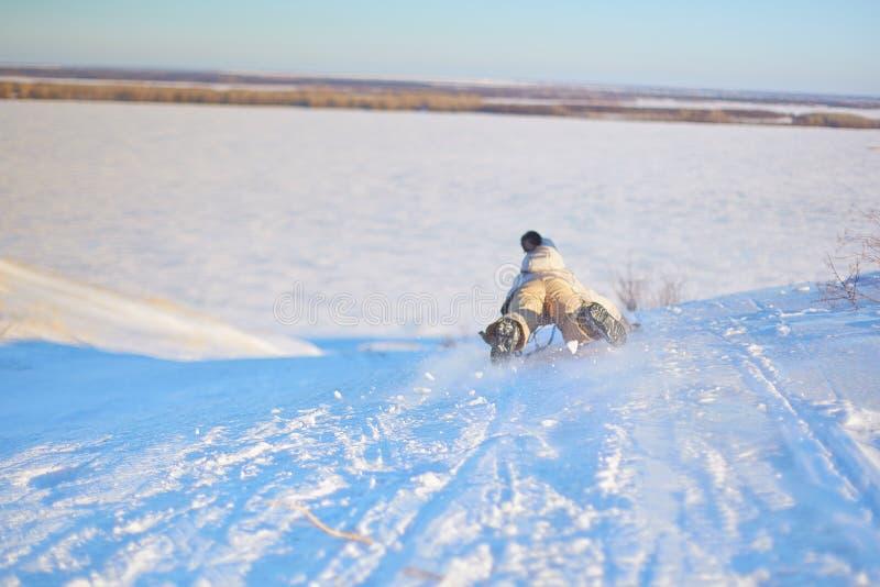 乘坐雪撬的快乐的女孩下坡在一个白色晴朗的冬天山风景的一串积雪的爬犁足迹 免版税库存照片