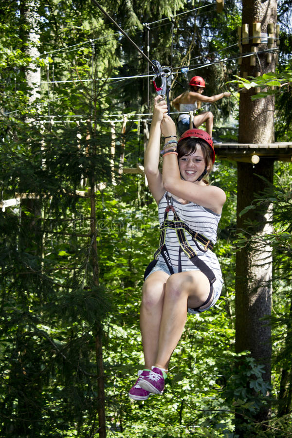 乘坐青少年的zipline的森林女孩 免版税库存图片