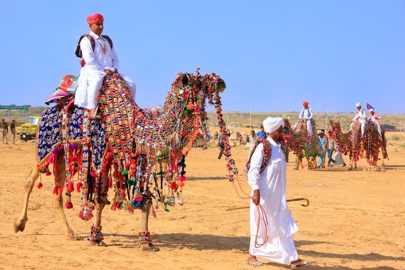 乘坐骆驼在沙漠节日, Jaisalmer,印度的地方人 库存照片