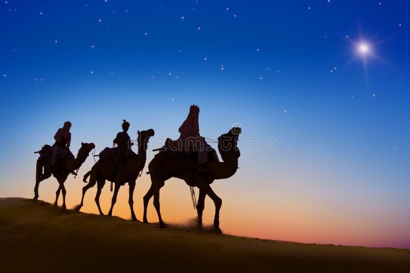 乘坐骆驼的三个圣人在小山 免版税库存照片