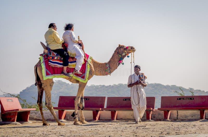 乘坐骆驼的印地安游人在Kalo Dungar, Kutch,印度 库存图片