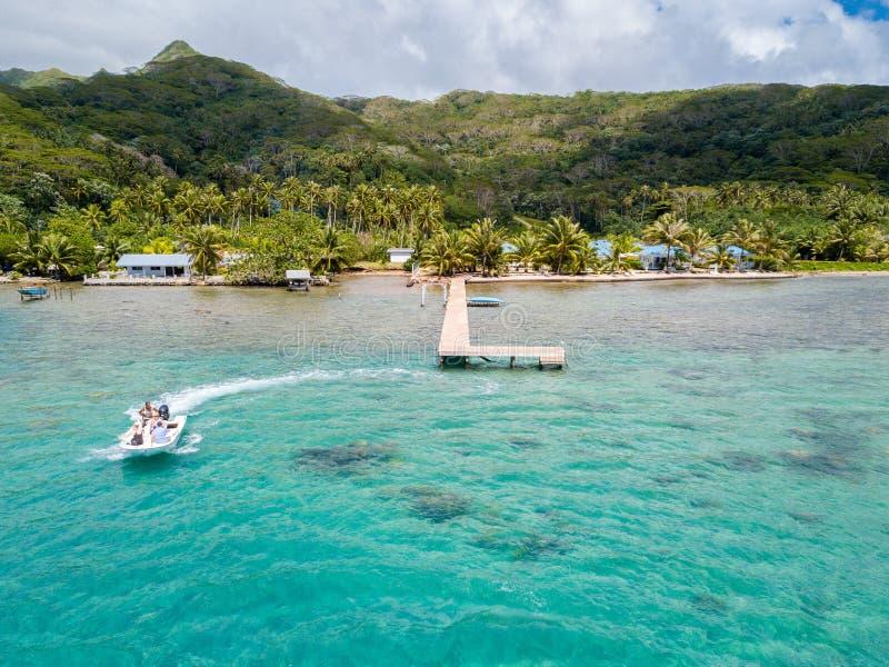 乘坐高速喷气机小船的游人在一个惊人的天蓝色的蓝色绿松石盐水湖 鸟瞰图 Raiatea,法属玻里尼西亚 库存照片