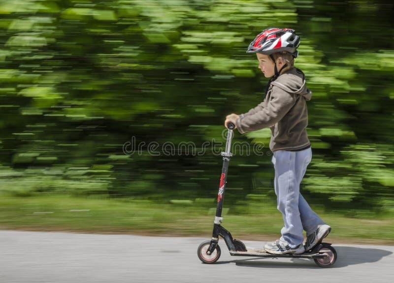 乘坐他的滑行车的男孩 免版税库存照片