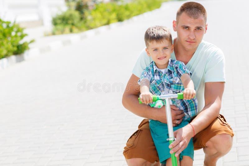 乘坐滑行车的父亲教的儿子 库存照片