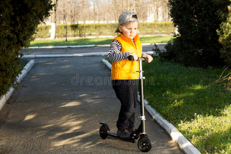 乘坐滑行车的年轻男孩 免版税库存照片