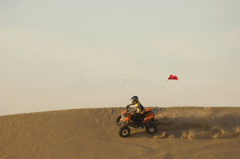 乘坐Atv的人在沙漠 免版税库存图片