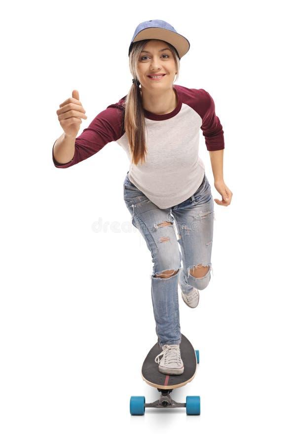 乘坐longboard的女性溜冰者 库存照片