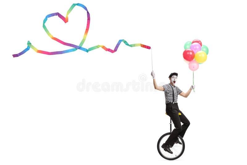 乘坐monocycle和拿着与心形和一束的年轻笑剧一条丝带五颜六色的气球 免版税图库摄影