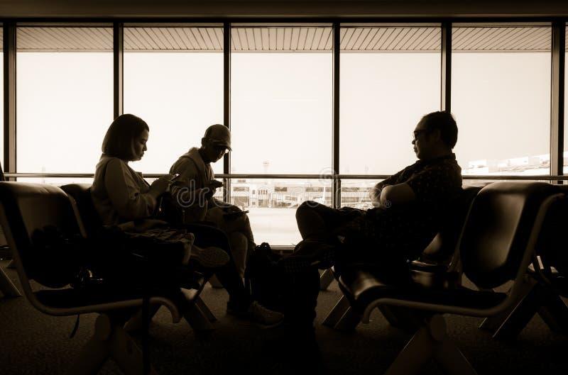 乘客剪影在室坐在机场终端 免版税库存图片