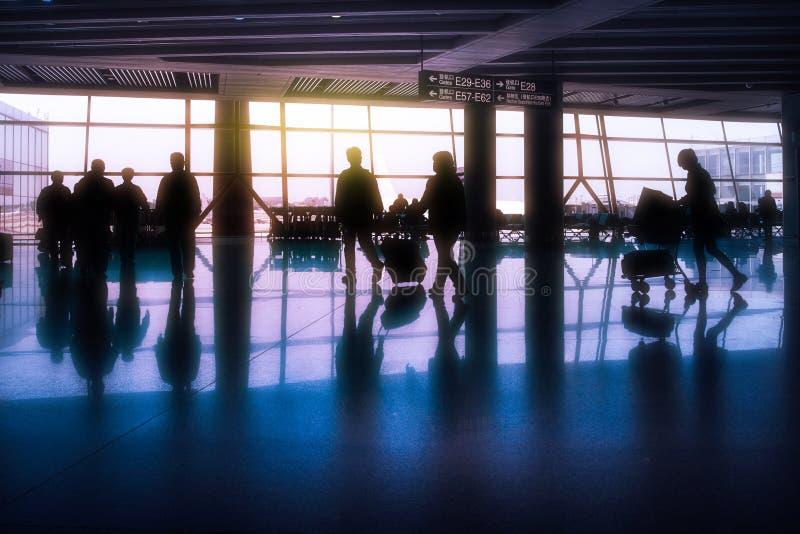 乘客剪影在有太阳shini的一个亚洲机场 免版税库存图片