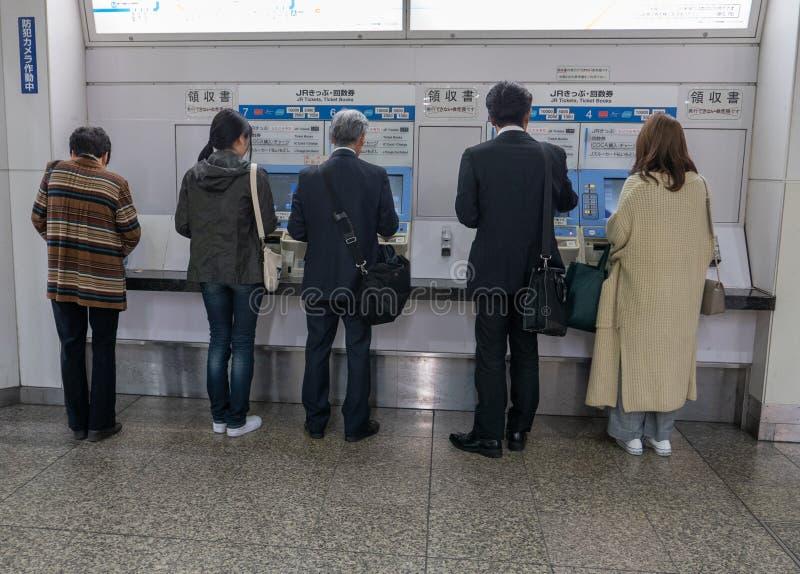 乘客在神户,日本购买从自动化的票机器的火车票 免版税库存照片