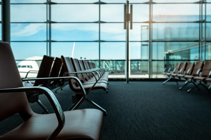 乘客座位在机场终端的离开休息室 机场终端内部  椅子在国际离开区域 免版税库存图片