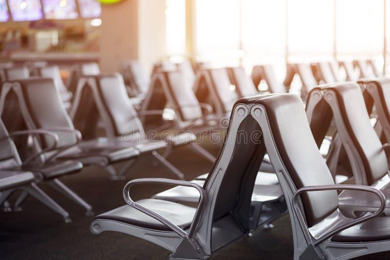 乘客座位在离开休息室为看见飞机,等待的大厅,从机场终端的看法 运输和旅行概念 免版税图库摄影