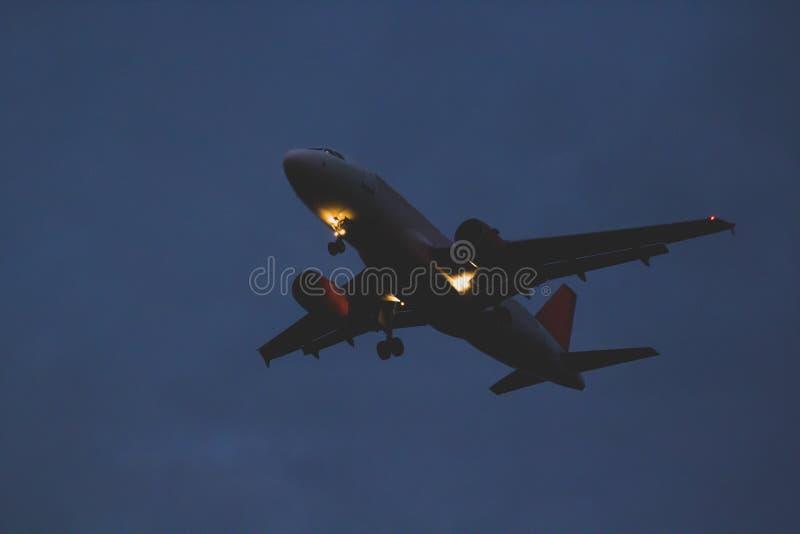 乘客或货机飞行到黑暗的天空在ev的黄昏 免版税库存图片