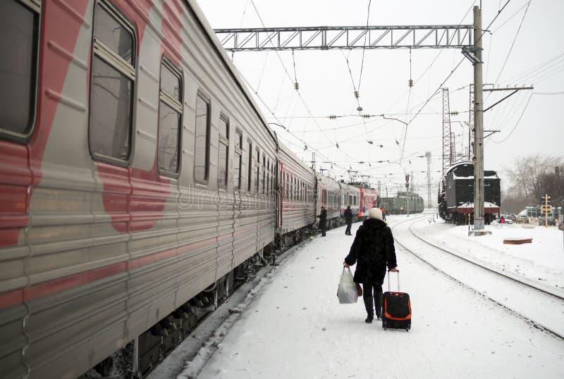 乘客是在沿火车的火车站平台冬天 免版税库存图片
