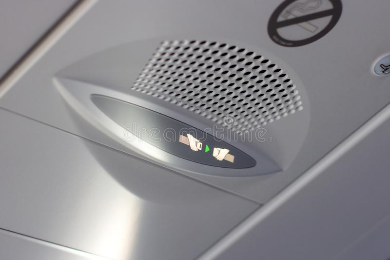乘客的注意公告紧固您的在信息委员会的游乐器具标志在飞机客舱里面 库存照片