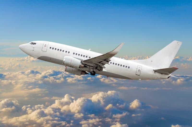 乘客飞机在云彩上的天空爬升飞行 免版税库存图片
