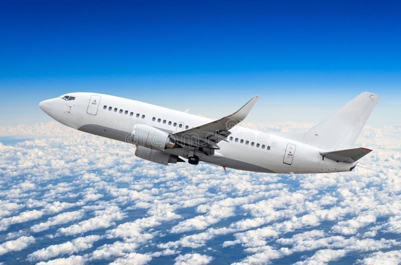 乘客飞机在云彩上的天空爬升飞行 图库摄影