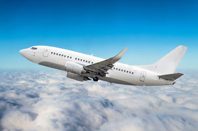 乘客飞机在云彩上的天空爬升飞行 免版税图库摄影