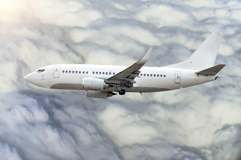乘客飞机在云彩上的天空爬升飞行 库存照片