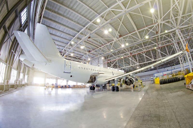 乘客飞机在引擎,机体维护和在辅助电源设备 在机场飞机棚检查修理 航空器图t 库存照片