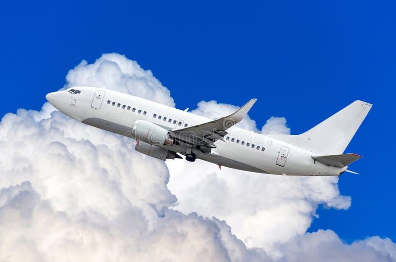 乘客飞机在积云上的天空上升的高度飞行 免版税库存照片
