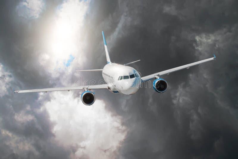 乘客飞机通过动荡区域飞行通过暴风云闪电在恶劣天气的 免版税库存照片