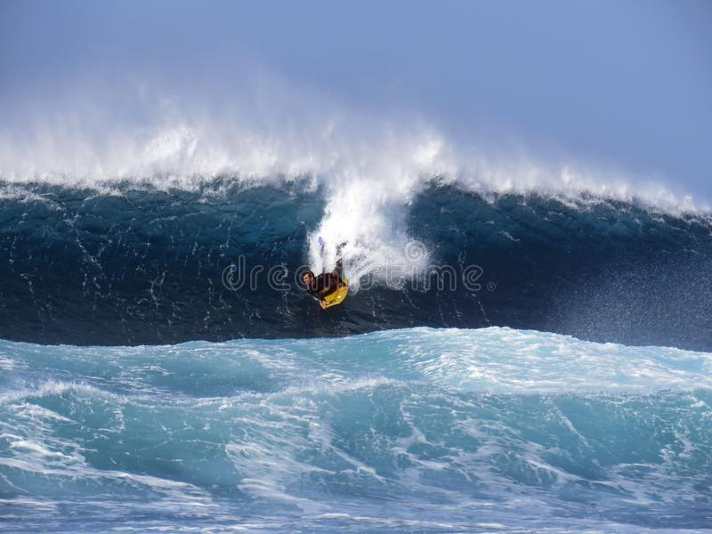 乘巨大的大西洋波浪的冲浪者 库存图片