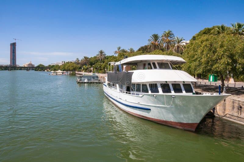 乘快艇在瓜达尔基维尔河河的一个码头在塞维利亚 库存图片