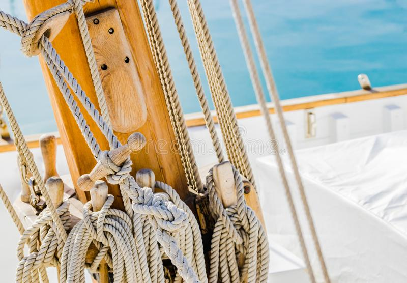 乘快艇,在古典帆船甲板的木帆柱栓的装配的船舶绳索  免版税库存照片