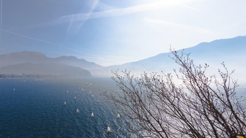 乘快艇 有游艇sailer船航行的风景全景由在平衡日落太阳光束的湖或海波浪 捕鱼 免版税库存图片