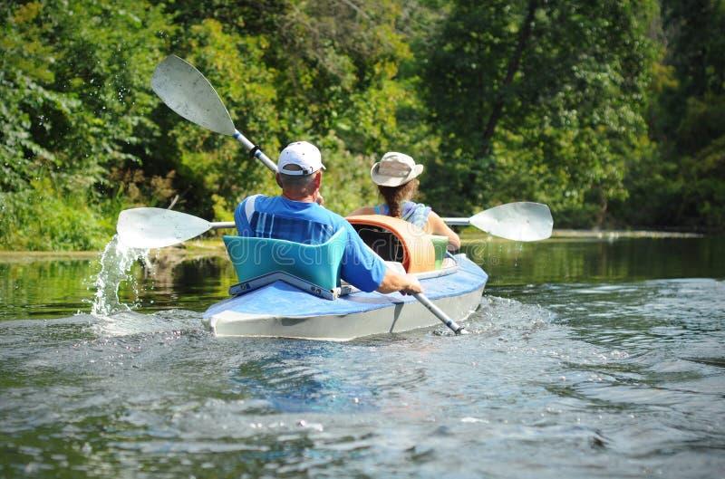 乘独木舟在一条小河的人们在夏天 库存图片