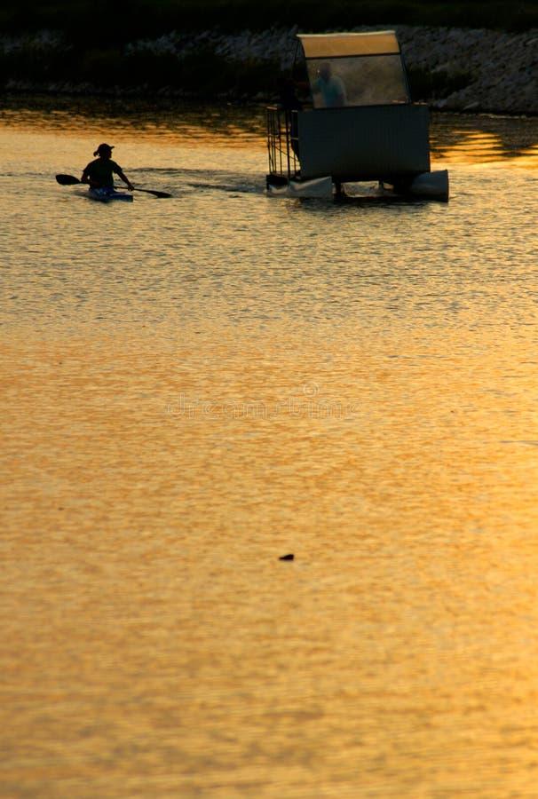 乘独木舟在日落 库存照片