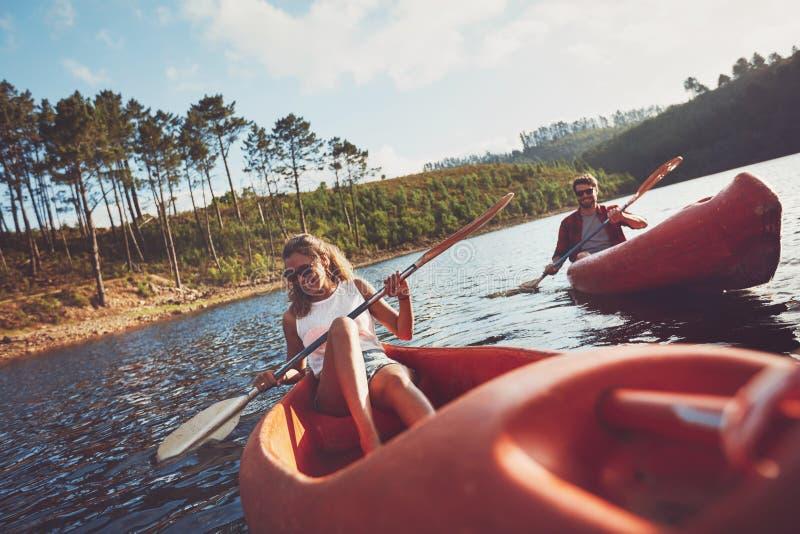 乘独木舟在湖的愉快的年轻夫妇 免版税图库摄影