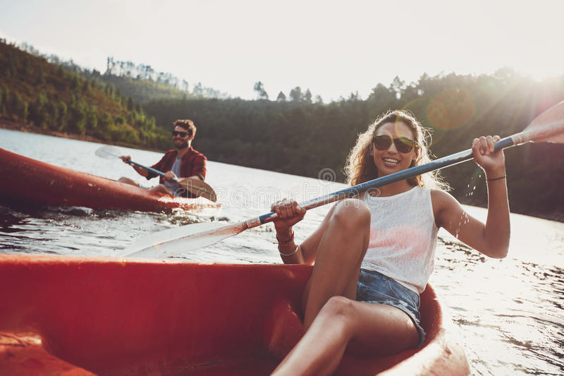 乘独木舟在湖的青年人 图库摄影