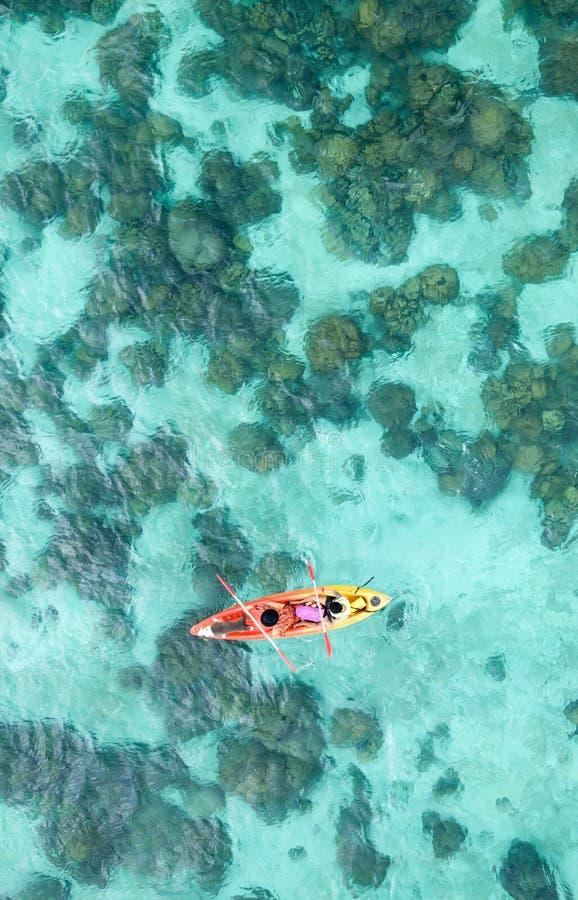 乘独木舟或划皮船在海海岛backdro的夫妇鸟瞰图  库存图片
