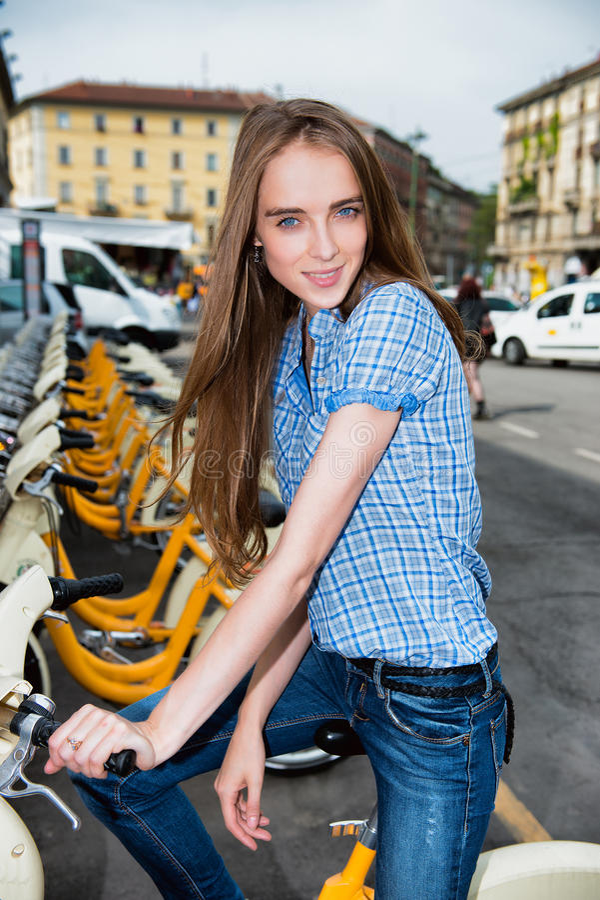 乘租自行车的美丽的妇女在城市 免版税库存图片