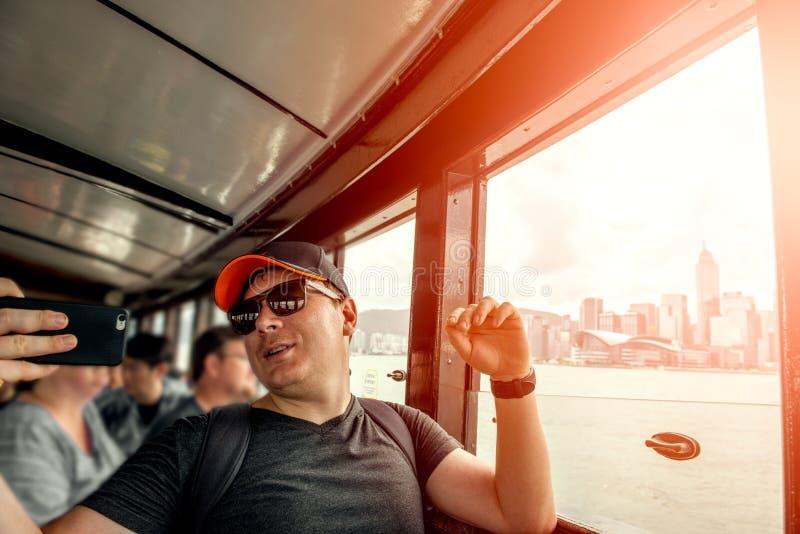 乘轮渡在香港和使用手机的旅客拍照片 免版税库存图片
