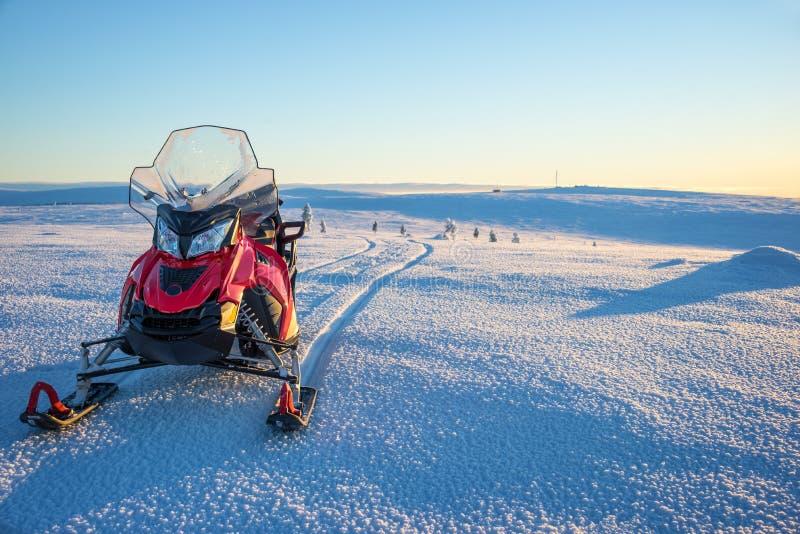 乘雪上电车在一个多雪的风景在拉普兰在Saariselka,芬兰附近 免版税库存图片