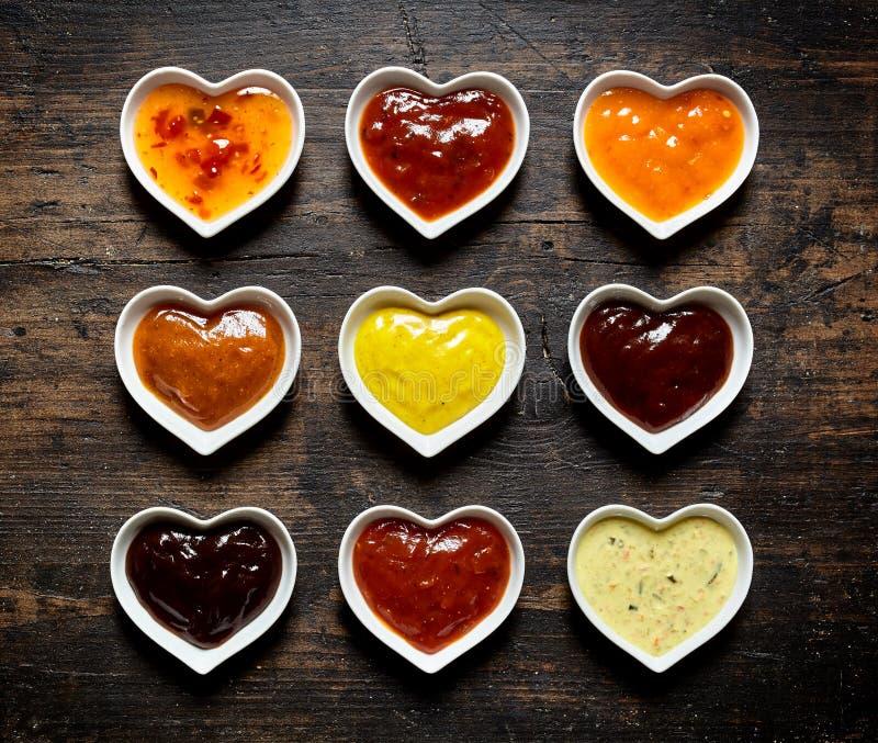 九个五颜六色的调味汁和卤汁在心形的碗 库存图片