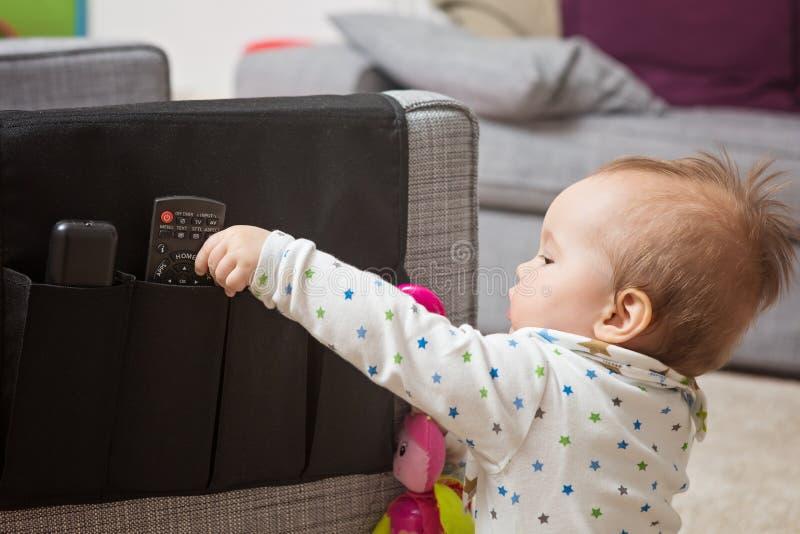 九个月女婴劫掠遥控 库存照片