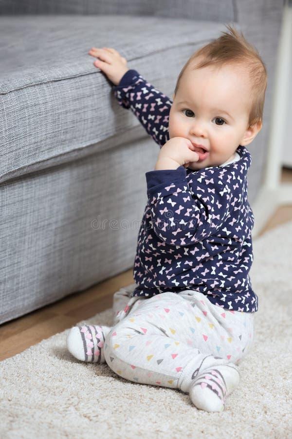 九个月女婴坐地板 库存图片