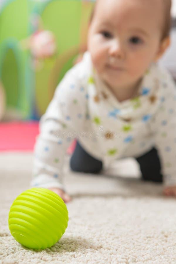 九个月爬行在地板上的女婴 免版税库存照片