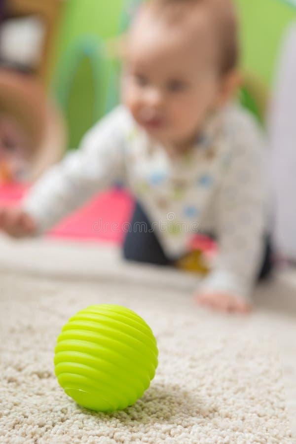 九个月爬行在地板上的女婴 库存照片