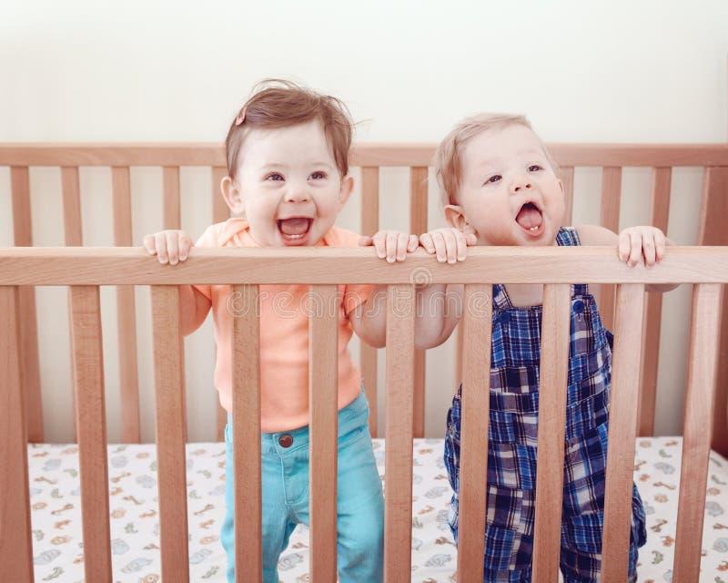 九个月的两个逗人喜爱的可爱的滑稽的小兄弟姐妹朋友画象站立在床小儿床微笑的笑的 库存图片
