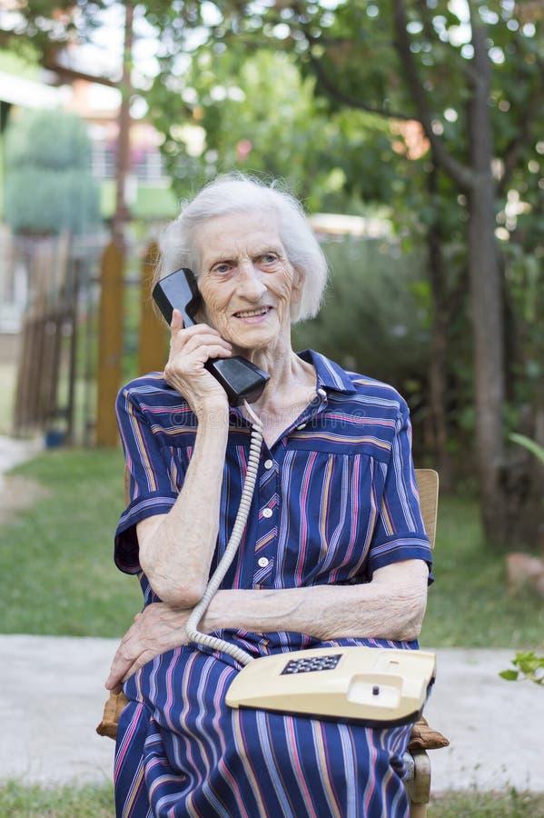 九十个岁夫人谈话在电话在后院 免版税库存照片