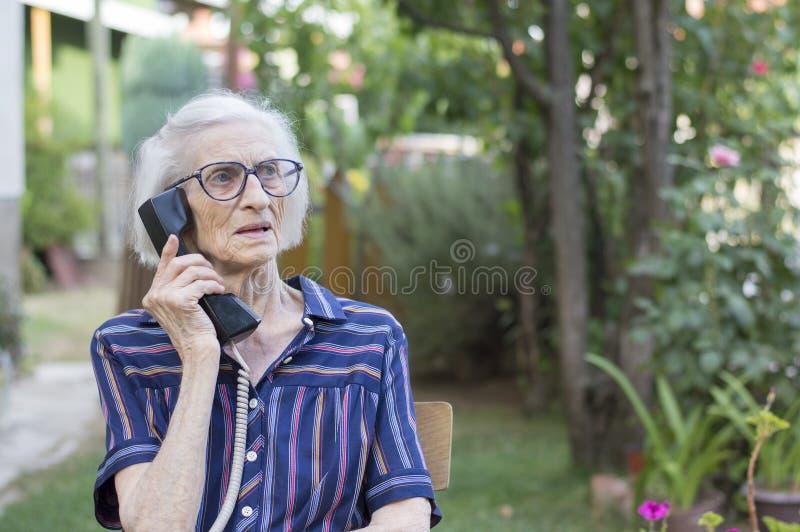 九十个岁夫人谈话在电话在后院 库存照片