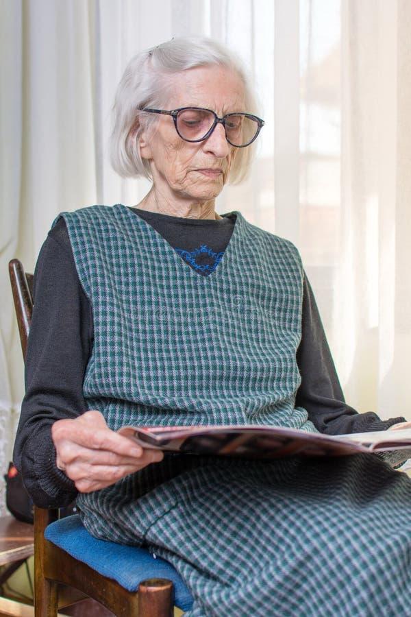 九十张岁夫人读书报纸 免版税图库摄影