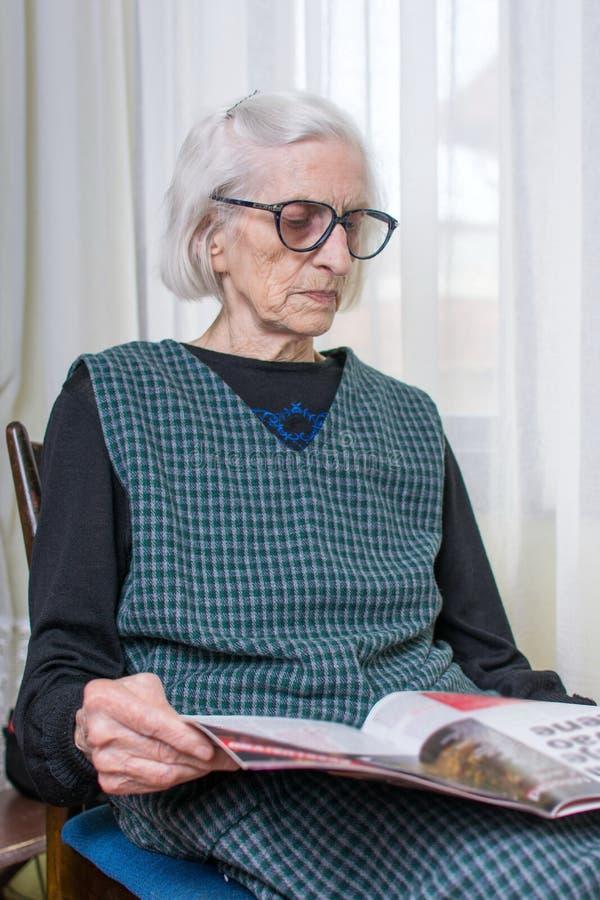 九十张岁夫人读书报纸 免版税库存照片